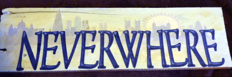 Sillhouette of London behind letters, mirrored below in a lighter blue