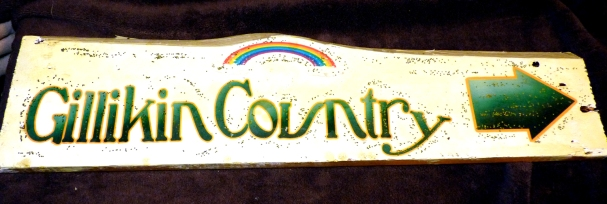 Rainbow and emerald green lettering ringed in gold